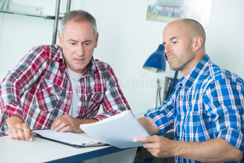 Serious upset worried men sitting with business papers. Contract royalty free stock photos