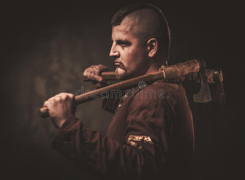 Serious viking with ax in a traditional warrior clothes, posing on a dark background. royalty free stock image