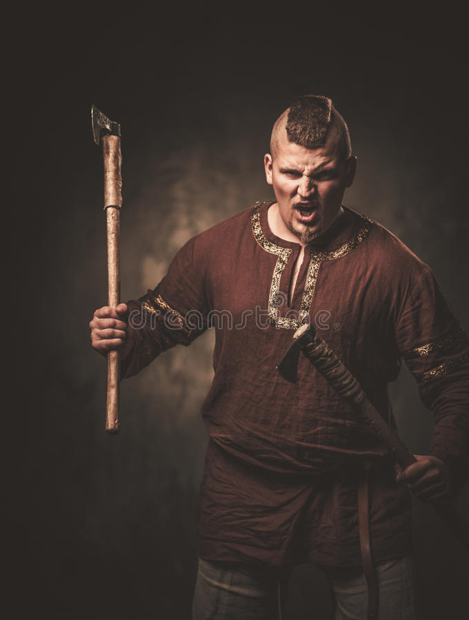 Serious viking with axes in a traditional warrior clothes, posing on a dark background. Angry viking with axes in a traditional warrior clothes, posing on a stock photography