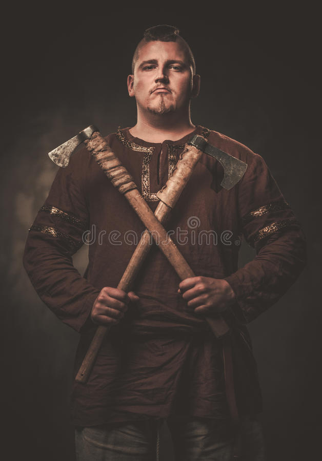 Serious viking with axes in a traditional warrior clothes, posing on a dark background. stock images