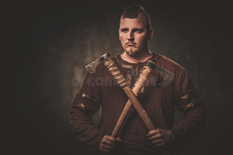 Serious viking with axes in a traditional warrior clothes, posing on a dark background. Angry viking with axes in a traditional warrior clothes, posing on a royalty free stock images