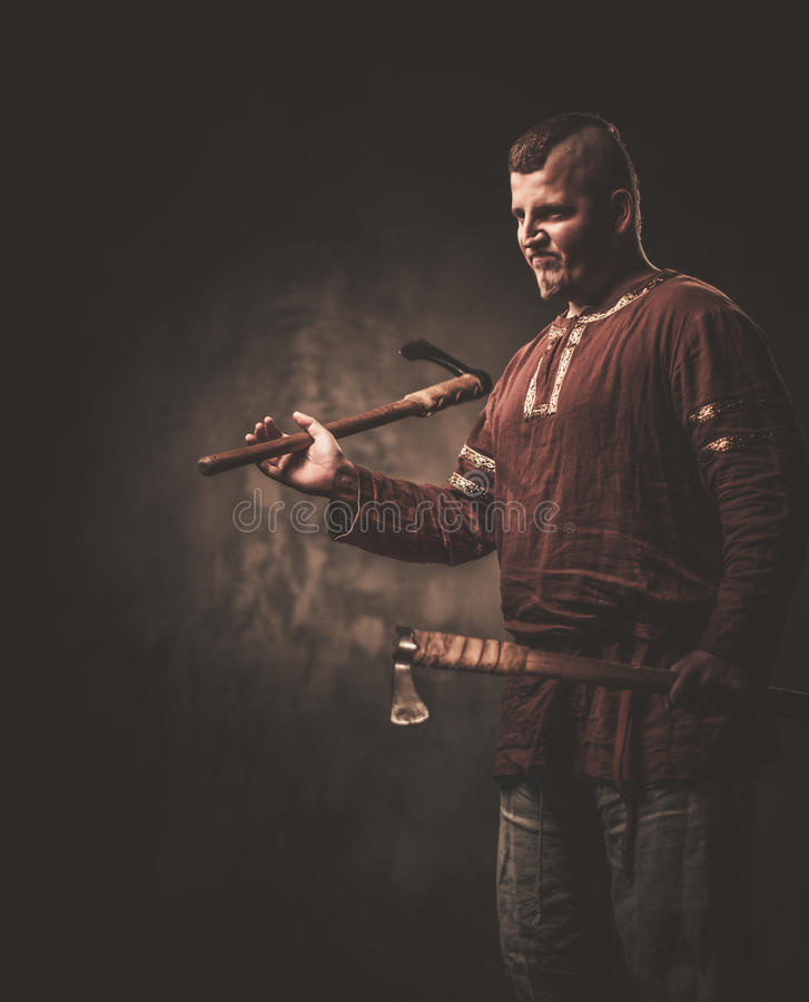 Serious viking with axes in a traditional warrior clothes, posing on a dark background. Angry viking with axes in a traditional warrior clothes, posing on a stock photo