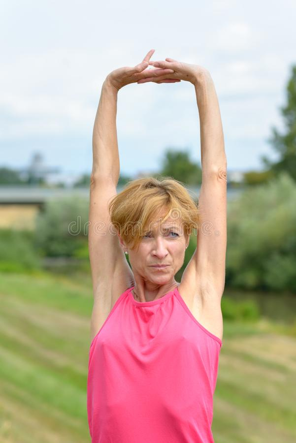Serious vivacious woman stretching her arms stock images