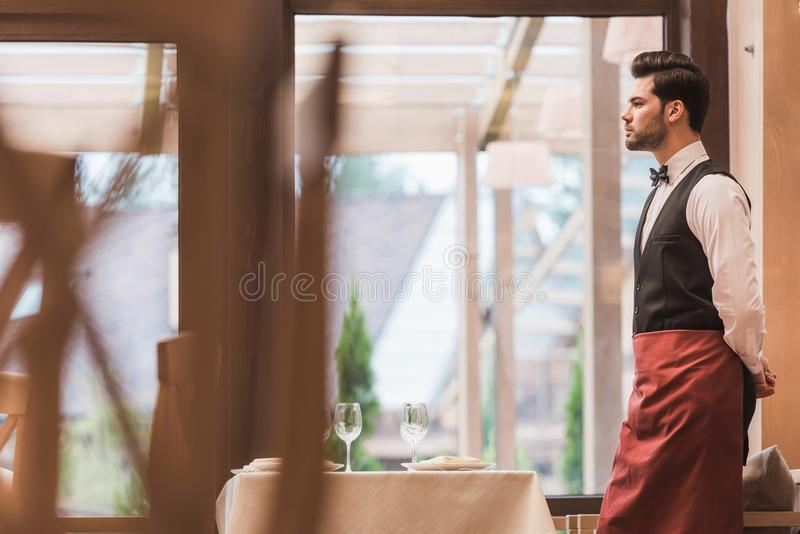Waiter standing near empty table stock photography