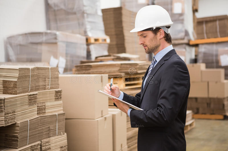 Serious warehouse manager checking inventory. In warehouse royalty free stock photos