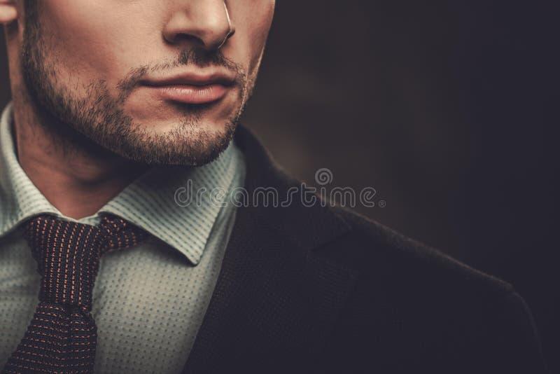 Serious well-dressed hispanic man posing. On dark background royalty free stock image