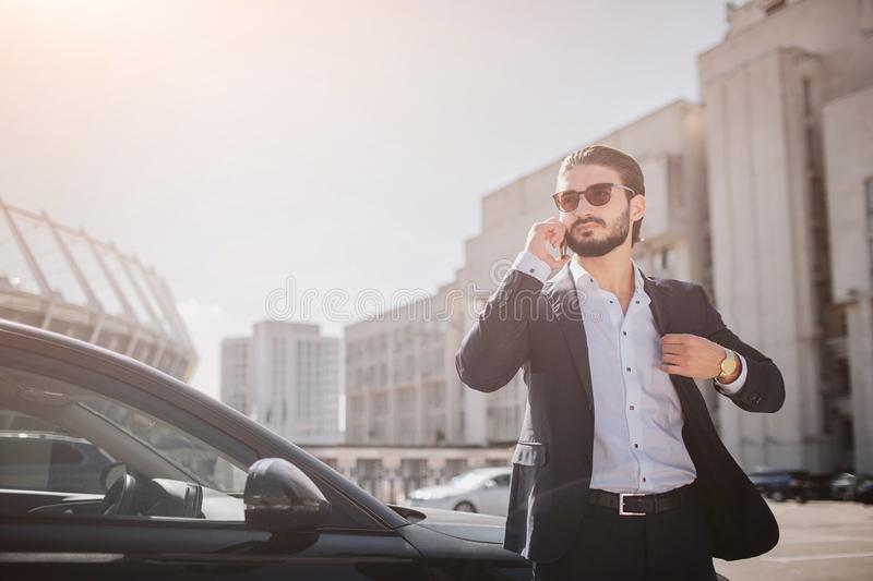 Serious and well-dressed young man stand at car in suite and talks on phone. He holds part of balck jacket. Guy wears stock photography