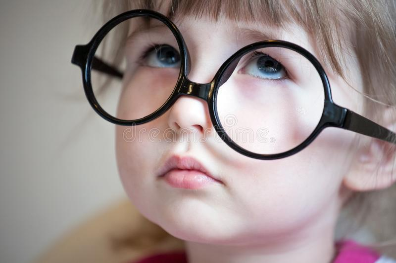 Serious white child girl in big black glasses royalty free stock images