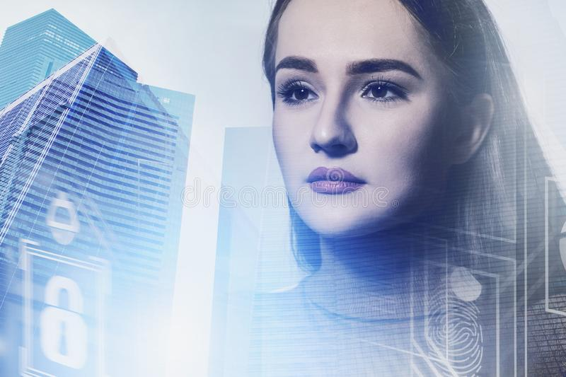 Serious woman in city, business interface. Serious young businesswoman in casual clothes standing in modern city with double exposure of business interface stock images