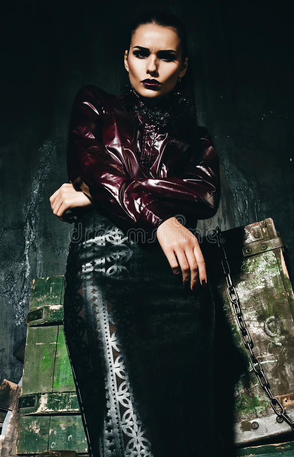 Serious woman in claret shirt and black leather skirt. In old interior stock photos