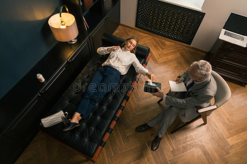 Serious woman discussing psychological problems with a psychotherapist. Heart-to-heart talk. Top view of a serious women lying on the sofa while discussing her stock image