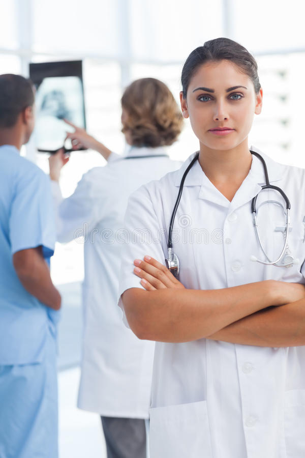 Serious woman doctor with arms crossed looking at the camera. Serious women doctor with arms crossed looking at the camera in front of medical team royalty free stock photo