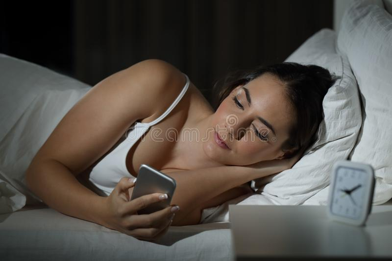 Serious woman holding smart phone on the bed stock images