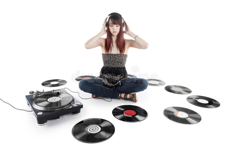 Serious Woman Listening Music on a Vinyl Turntable. Serious Young Pretty Woman Sitting on the Floor Listening Music on a Vinyl Turntable with Vinyl Records royalty free stock photography