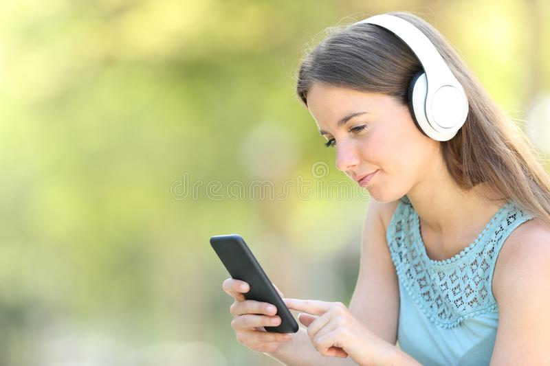 Serious woman listening to music using smart phone. In a park with a green background stock images