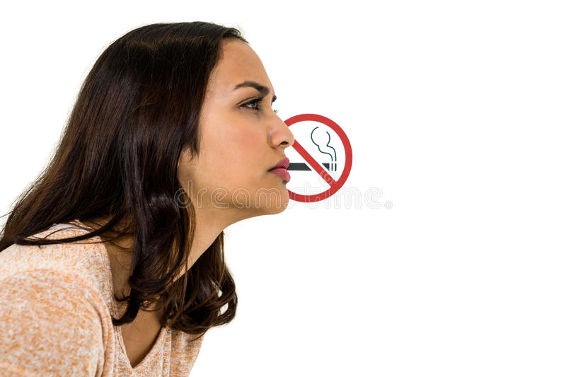 Serious woman looking away with no smoking sign. Over white background stock image