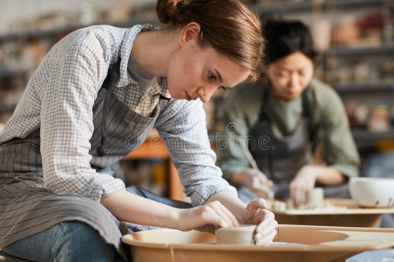 Serious woman making pot in workshop. Serious concentrated young women sitting at pottery wheel and adjusting edges of clay vessel while making pot in workshop royalty free stock photo