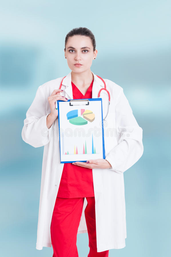 Serious woman medic with clipboard. In hand as profit analysis concept isolated on blue background royalty free stock images