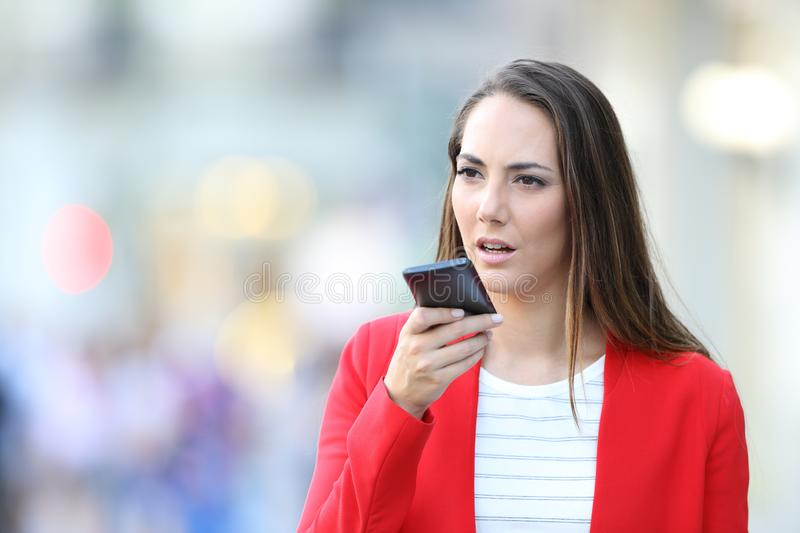 Serious woman in red using voice recognition on phone stock photo