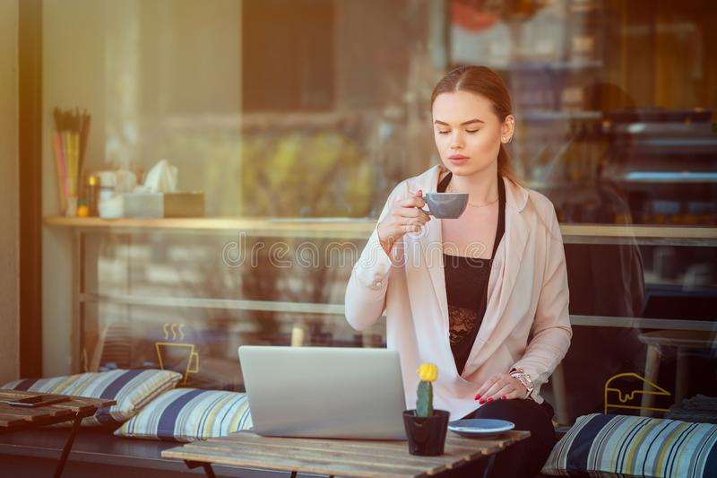 Serious woman sitting at cafe terrace holding coffee mug working on laptop royalty free stock images