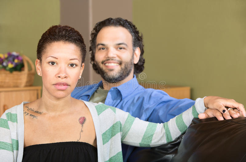 Serious Woman and Smiling Man. Smiling men sitting with serious Black woman stock image