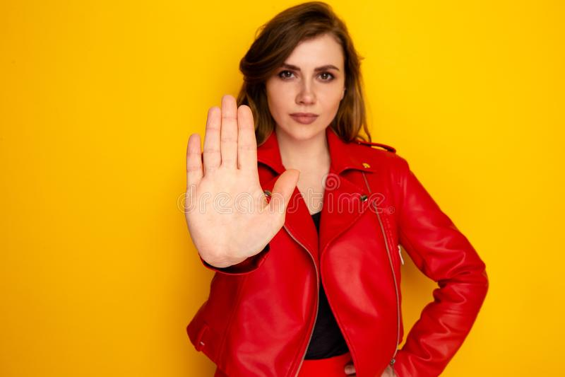 Serious woman standing with hand showing stop isolated on the yellow background. royalty free stock images