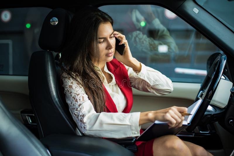 Serious woman successful business owner in formal wear checks in textbook the employment schedule and talking via mobile phone royalty free stock photos