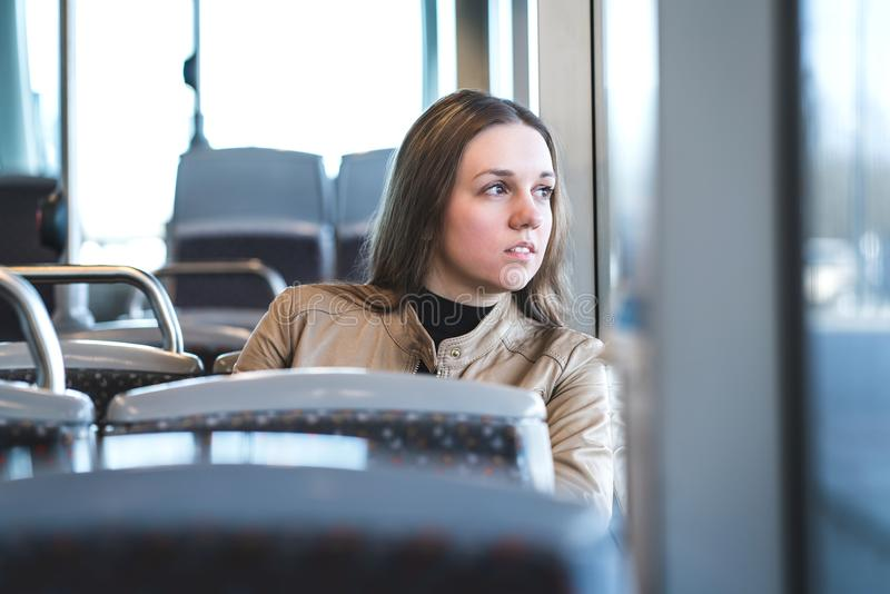Serious woman in train or bus looking through the window royalty free stock images