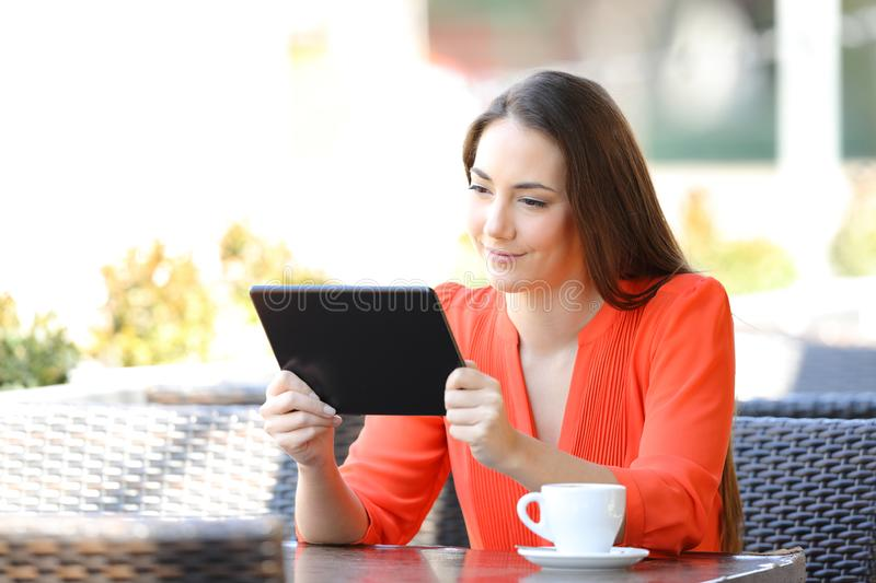 Serious woman watching tablet online content in a bar royalty free stock photos