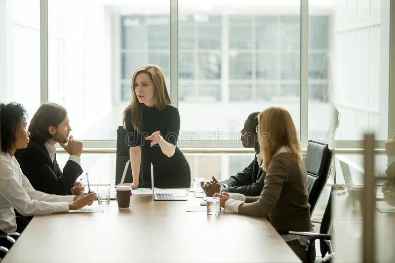 Serious woman boss talking to multiracial team at boardroom meet stock image