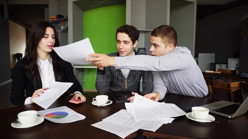 Serious workers and businessmen, two guys and girl discuss about royalty free stock image