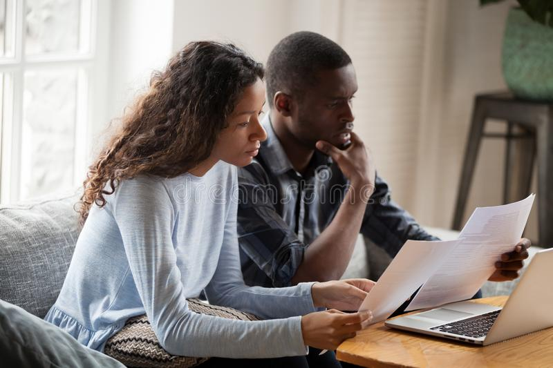 Serious worried african american couple reading documents at hom. Serious worried african american couple reading documents consider mortgage loan insurance royalty free stock images