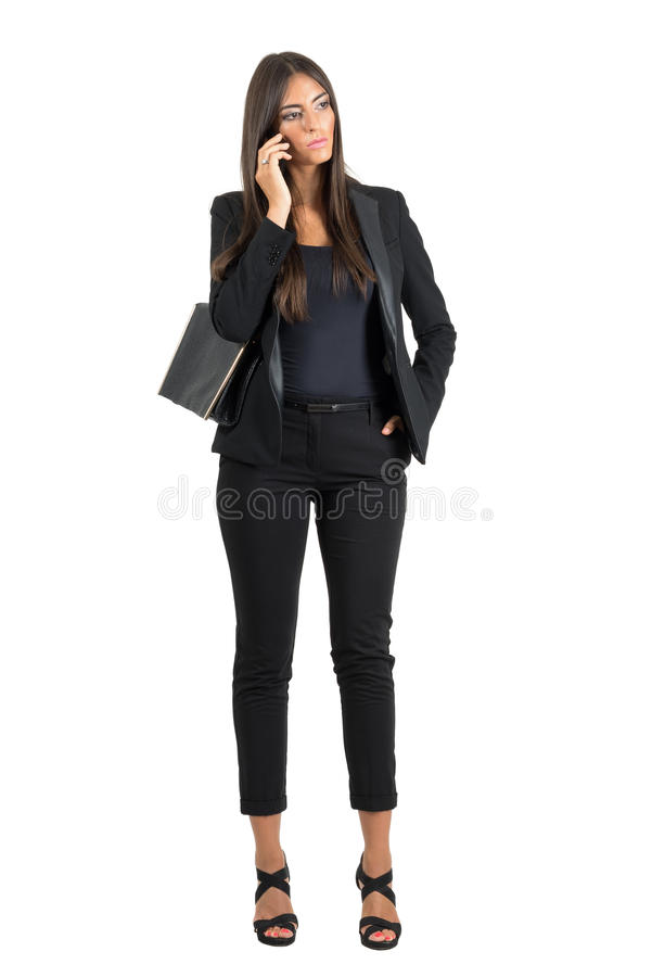 Serious worried business woman in suit talking on the mobile phone looking down. stock photos