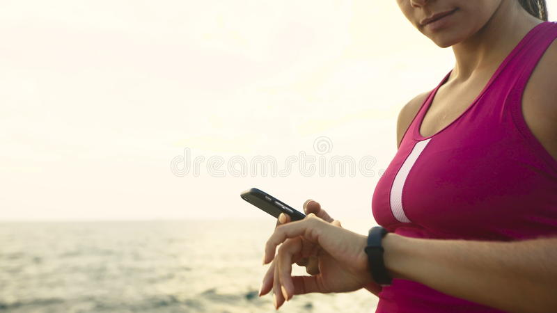 Serious young active woman checking miles on her running watch. stock images