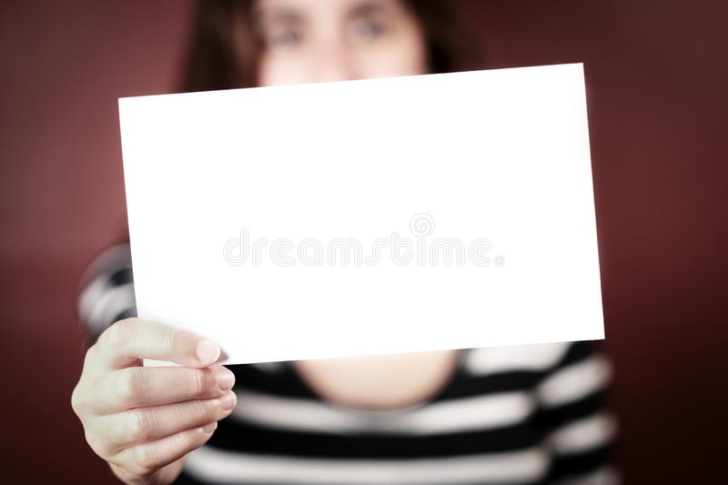 Serious young adult woman holding a blank sign stock photo