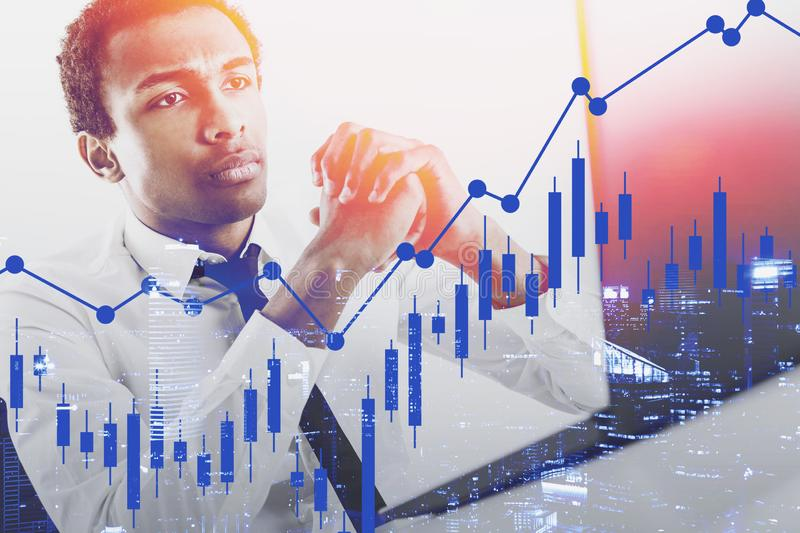 Serious African broker, forex charts. Serious young African American broker looking at laptop screen with double exposure of forex graph and night cityscape stock photos