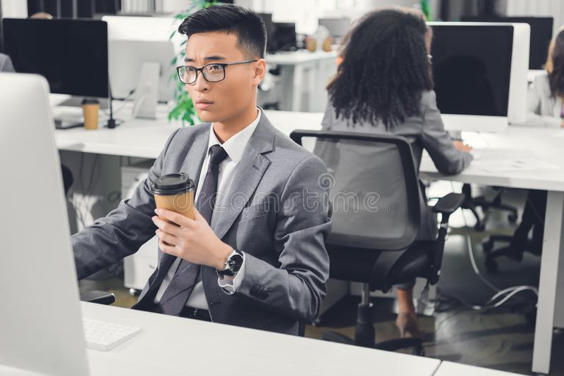 Serious young asian businessman holding coffee to go in using desktop computer stock image