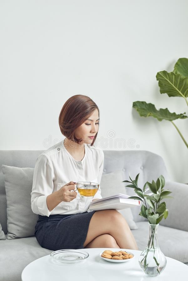 Serious young Asian girl in blouse and skirt.sitting on sofa and drinking tea while reading book in living room royalty free stock photography