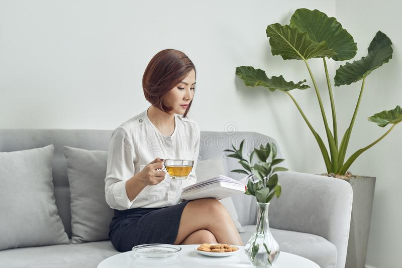 Serious young Asian girl in blouse and skirt.sitting on sofa and drinking tea while reading book in living room royalty free stock photo