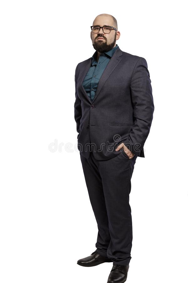 Serious young bald man in glasses with a beard, full height. Isolated on a white background stock photo