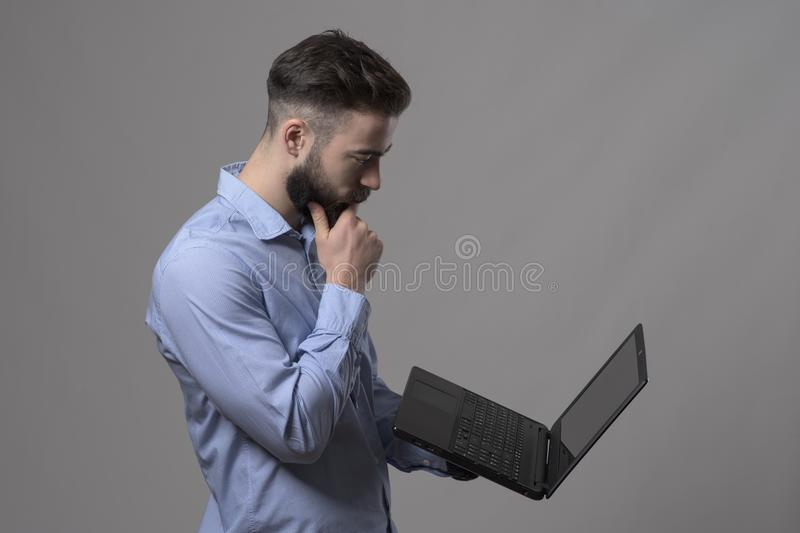 Serious young bearded business man looking at laptop computer and thinking stock photos