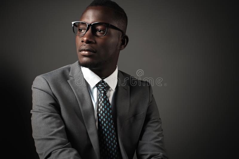 Serious young black man with glasses and gray business suit royalty free stock images