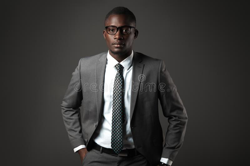 Serious young black man with glasses and gray business suit. Emotional business portrait stock photos