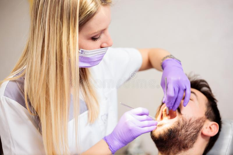Young female dentist examining male patient in dental clinic stock image