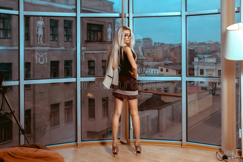 Serious young blonde business lady posing near large window with stock images