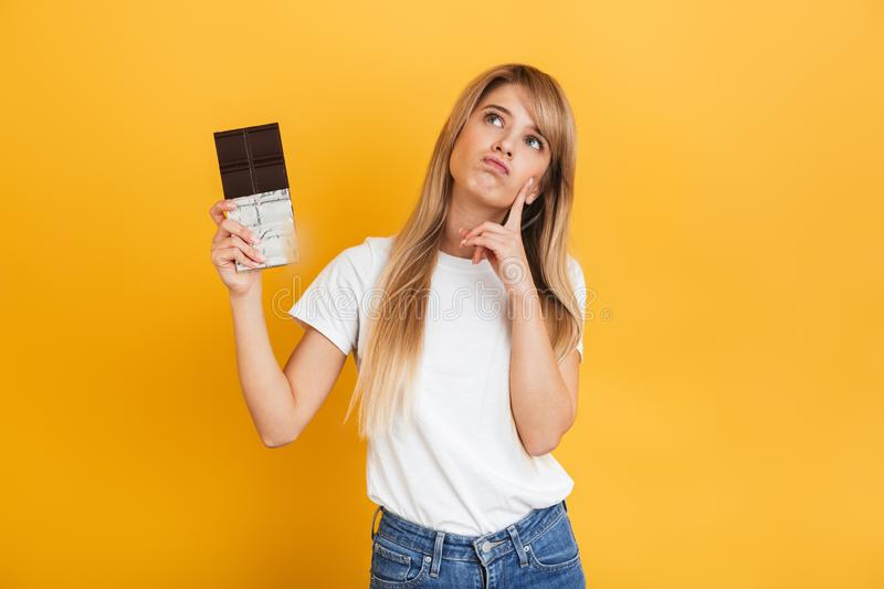Serious young blonde woman posing isolated over yellow wall background dressed in white casual t-shirt holding chocolate sweeties. Photo of a thinking young royalty free stock photography