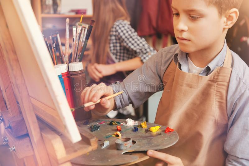 Serious young boy painting on art canvas royalty free stock photos