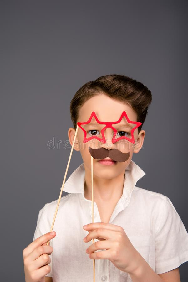 Serious young boy posing with paper mustache and glasses like stars royalty free stock photos