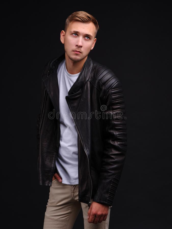 A guy in a white T-shirt and leather jacket, looks up. stock images
