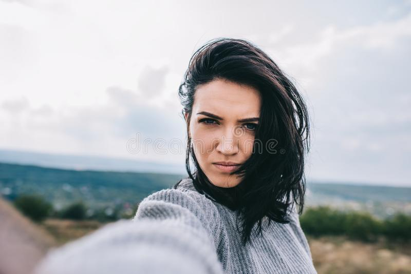 Serious young brunette woman taking self portrait and posing against meadow and overcast sky background. Cute female take selfie. From her device. People stock photo